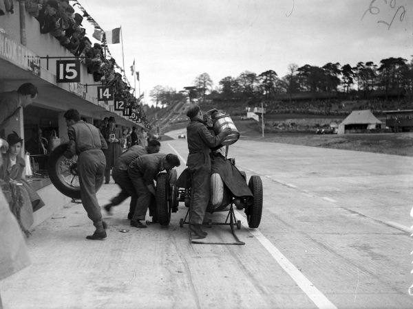 A car is refuelled and the tyres changed during a pitstop.