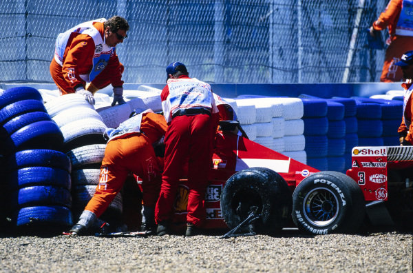 Marshals attend to Michael Schumacher, Ferrari F399, after he crashed heavily at Stowe corner following a brake failure. The resulting leg injuries sidelined him for the next six races.