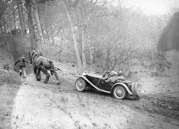 A car is towed up an incline by a horse.