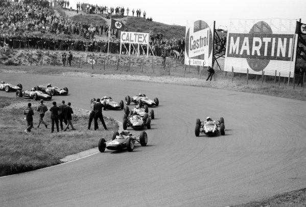 1963 Dutch Grand Prix Zandvoort, Holland. 21-23 June 1963 Jim Clark (#6 Lotus 25-Climax) leads Bruce McLaren (#20 Cooper T66-Climax), Graham Hill (#12 BRM P57), Jack Brabham (#16 Brabham BT7-Climax), Tony Maggs (#22 Cooper T66-Climax), Richie Ginther (#14 BRM P57), John Surtees (#2 Ferrari 156), Jo Bonnier (#28 Cooper T60-Climax) and Trevor Taylor (#8 Lotus 25-Climax) into Tarzan Corner at the start. Clark finished in 1st position World Copyright: LAT PhotographicRef: Autosport b&w print