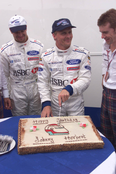 FRENCH GRAND PRIX. 25th June 1999. MAGNY-COURS, FRANCE JOHNNY HERBERT CUTS HIS BIRTHDAY CAKE World - LAWRENCE/LAT Photographic