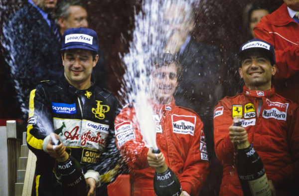 Alain Prost, 1st position, Michele Alboreto, 2nd position, and Elio de Angelis, 3rd position, celebrate on the podium with champagne.