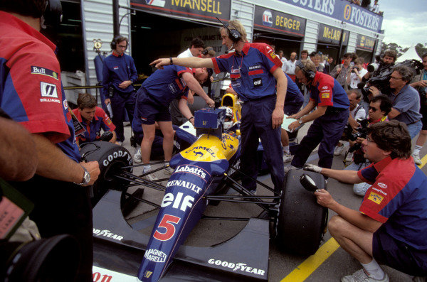 Nigel Mansell sits in his Williams FW14 Renault in the pits as mechanics work on the car.