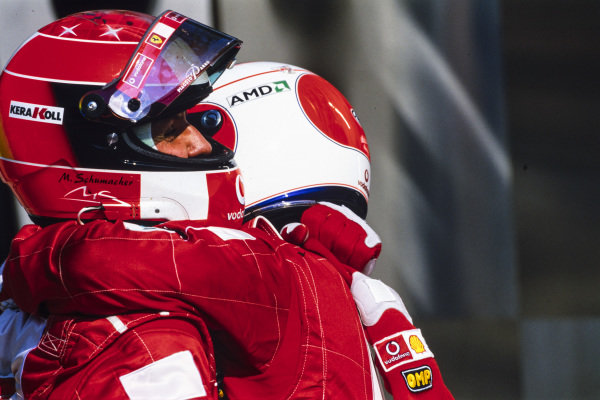 Rubens Barrichello hugs Michael Schumacher in Parc Ferme.