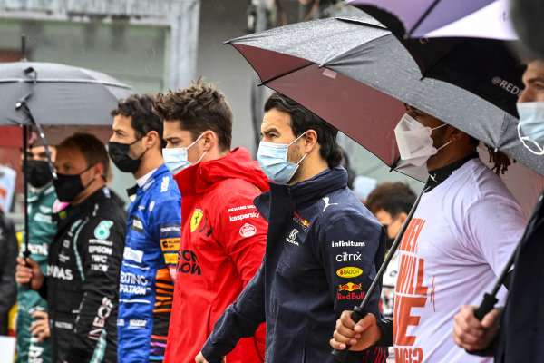Charles Leclerc, Ferrari, Sergio Perez, Red Bull Racing, Sir Lewis Hamilton, Mercedes, and the other drivers stand for the national anthem prior to the start