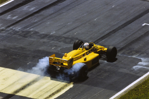 Satoru Nakajima, Lotus 99T Honda, leaves rubber on the track as he spins the rear wheels.