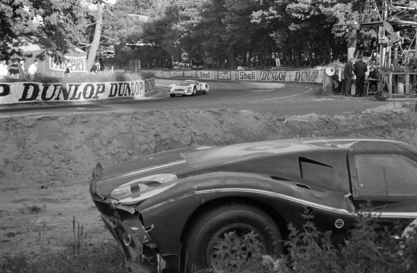 The abandoned Ford GT40 Mk4 of Lloyd Ruby / Denny Hulme in the foreground, as Vic Elford / Ben Pon, Porsche System Engineering, Porsche 906, passes in the background.