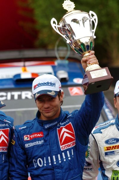 Sebastien Loeb (FRA) with the winner's trophy on the podium in Trier. FIA World Rally Championship, Rd9, Rally Germany, Trier, Germany, Day Three, Sunday 13 August 2006. DIGITAL IMAGE