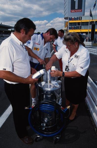 FIA stewards take an Elf fuel sample.