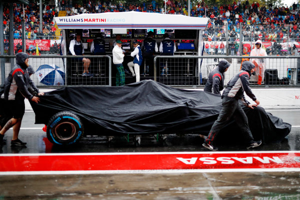 Haas team members push the car of Romain Grosjean, Haas VF-17, back into the pits as Sir Jackie Stewart, 3-time F1 Champion, and Felipe Massa, Williams Martini Racing, watch from the Williams Racing pit wall.