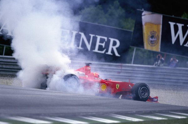 Michael Schumacher, Ferrari F1-2000, leaves a cloud of tyre smoke as he recovers from a spin during qualifying.