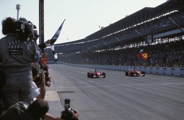 Rubens Barrichello, Ferrari F2002, passes teammate Michael Schumacher on the finish line. Schumacher slowed down at the end of the race.
