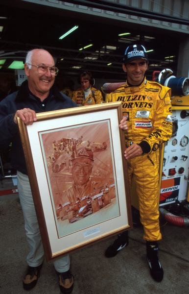 ITV F1 TV commentator Murray Walker (GBR) (left) is presented by Damon Hill (GBR) with a painting commemorating his fifty years of service to British Motorsport. Formula One World Championship, British GP, Silverstone, England, 12 July 1998