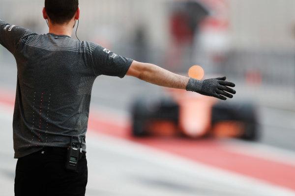 Bahrain International Circuit, Sakhir, Bahrain.  Wednesday 19 April 2017. A McLaren team member directs Stoffel Vandoorne, McLaren MCL32 Honda, into the pit lane. World Copyright: Glenn Dunbar/LAT Images ref: Digital Image _X4I4788