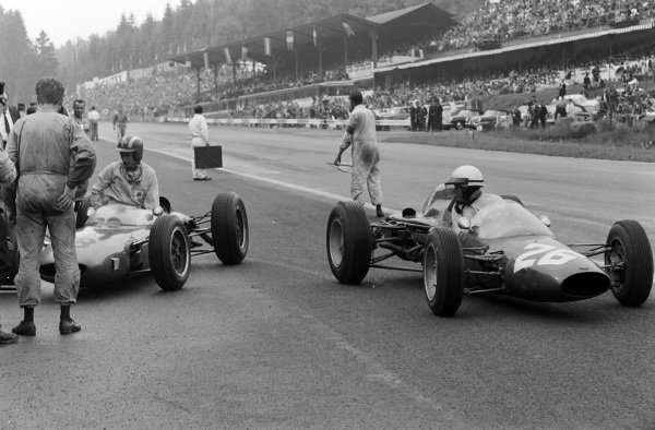 Phil Hill, A.T.S. 100, passes Jo Siffert, who is climbing out of his Lotus 24 BRM following his retirement.