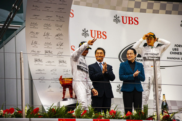 Lewis Hamilton, 1st position, arrives at the podium. Nico Rosberg, 2nd position, is also present.