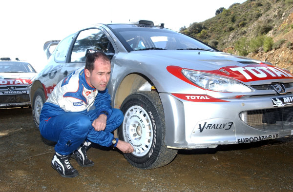 World Rally Championship, Cyprus Rally, April 18-21, 2002.Robert Reid checks the tyre pressures on his and Richard Burns' Peugeot 206 WRC before the first stage of the final day.Photo: Ralph Hardwick/LAT