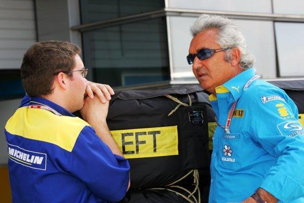 Flavio Briatore (ITA) Renault Team Principal (Right) talks with Michelin representative.Formula One World Championship, Rd16, Chinese Grand Prix, Preparations, Shanghai, China, 23 September 2004.DIGITAL IMAGE