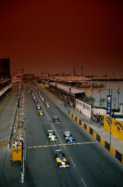 Under a red sky, Michael Schumacher (GER) leads the field from the start.  He won the first of two heats. International Formula Three, Macau Grand Prix, November 1989.