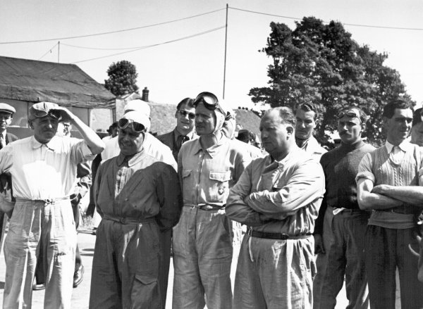 1949 British Grand Prix. Silverstone, Great Britain. 14 May 1949. Drivers briefing (left-to-right): Philippe Etancelin, Yves Giraud-Cabantous, Lord Selsdon (behind in dark glasses), Emmanuel de Graffenried (1st position), Fred Ashmore, Philip Fotheringham-Parker (behind), John Bolster, and Peter Walker. World Copyright: LAT Photographic
