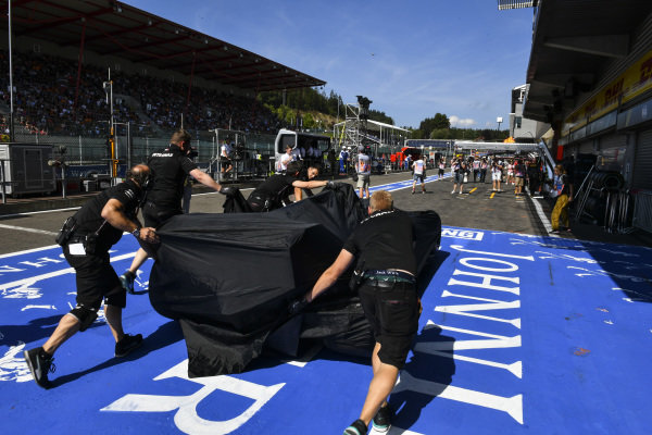 Mercedes engineers move the covered car of Lewis Hamilton, Mercedes AMG F1 W10, after its return to the pit lane