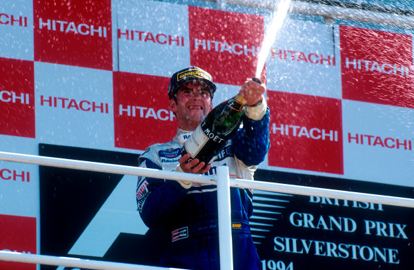 1994 British Grand Prix.Silverstone, England.8-10 July 1994.Damon Hill (Williams Renault) 1st position, celebrates with the bubbly on the podium.Ref-94 GB 16.World Copyright - LAT Photographic