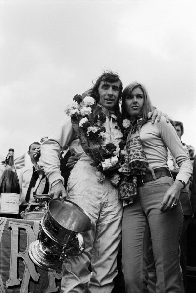 Winner Jackie Stewart celebrates victory on the podium with wife Helen.