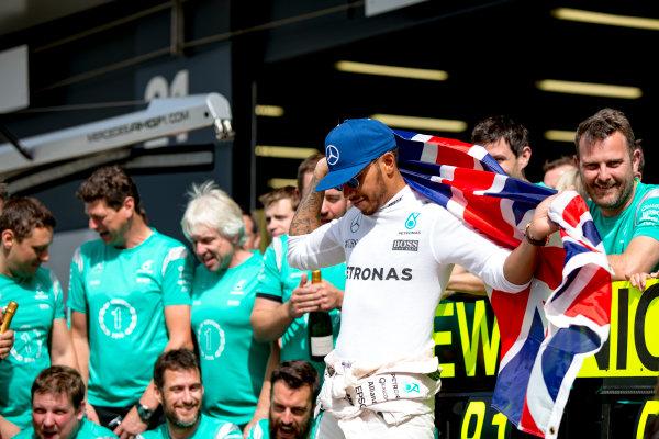 Silverstone, Northamptonshire, UK. Sunday 10 July 2016. Lewis Hamilton, Mercedes AMG, celebrates his win with the team. World Copyright: Zak Mauger/LAT Photographic ref: Digital Image _79P8681
