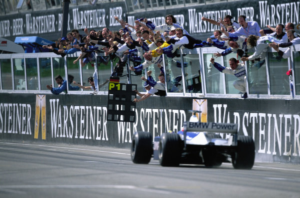 Ralf Schumacher, Williams FW23 BMW, and the team celebrate his maiden grand prix win.