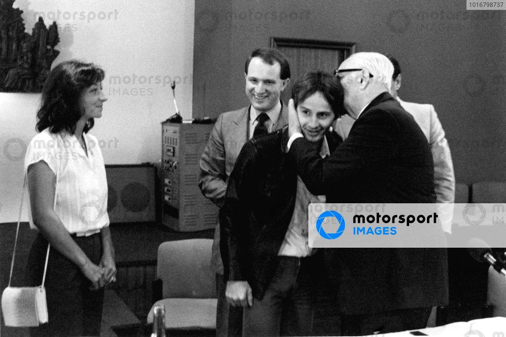 Joan Villeneuve smiles as Enzo Ferrari kisses Gilles Villeneuve, the day after Villeneuve's crash in the Italian Grand Prix at Imola.