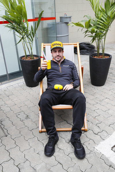 Fernando Alonso, McLaren, holds a drink while sitting on a deckchair for RTL.