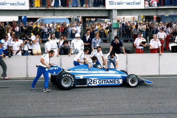 The Ligier team jump the pitwall and rush to Jacques Laffite (FRA) Ligier JS7 as he became the first all-French winner of an F1 GP.