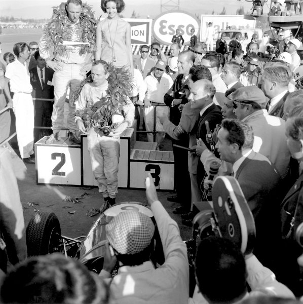 1964 Mexican Grand Prix.Mexico City, Mexico, 25 October 1964.John Surtees (Ferrari 158) celebrates on the podium as he becomes the only man to win World Championships on motorbikes and in a car. Racewinner Dan Gurney (Brabham BT7-Climax) looks on as does Stirling Moss. Ref-27505 40mb Scan from B&W PrintWorld Copyright: LAT Photographic