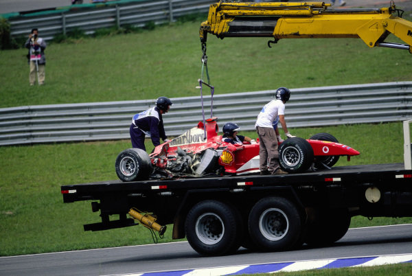 Michael Schumacher's Ferrari F2004 is recovered after a crash during practice.