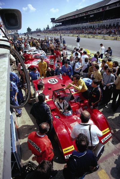Mauro Forghieri talks to his driver Jacky Ickx, while teammate Clay Regazzoni sits strapped in his S.p.A. Ferrari SEFAC, Ferrari 312 PB 0878.