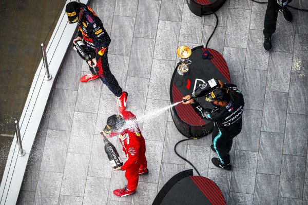 Carlos Sainz, Ferrari, 3rd position, Max Verstappen, Red Bull Racing, 2nd position, and Sir Lewis Hamilton, Mercedes, 1st position, spray Champagne on the podium