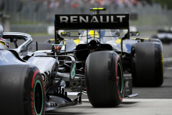 Nico Hulkenberg, Renault R.S. 19, leads Lewis Hamilton, Mercedes AMG F1 W10, out of the pits