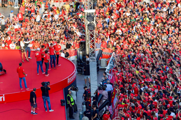 The Ferrari Academy drivers wave to the crowd from the stage