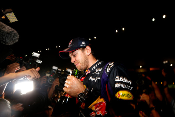 Buddh International Circuit, New Delhi, India. Sunday 27th October 2013. Sebastian Vettel, Red Bull Racing, 1st position, and the Red Bull team celebrate winning the drivers and constructors titles. World Copyright: Alastair Staley/LAT Photographic. ref: Digital Image _R6T9418