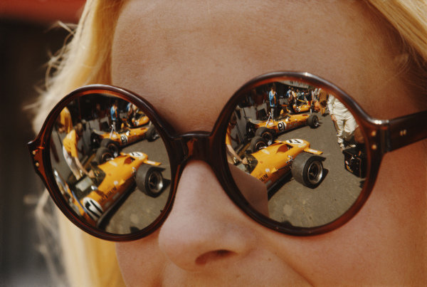 McLaren M14A Fords reflected in a woman's sunglasses in the pits.