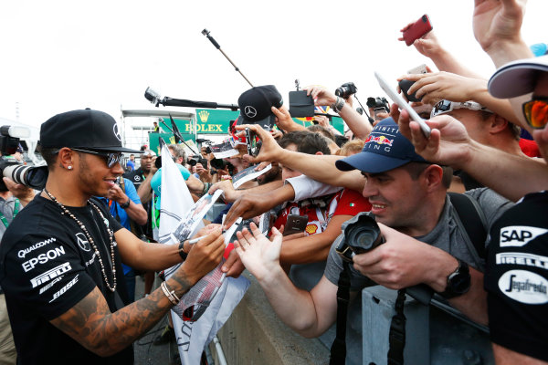 Circuit Gilles Villeneuve, Montreal, Canada. Sunday 7 June 2015. Lewis Hamilton, Mercedes AMG, 1st Position, celebrates with and signs autographs for fans. World Copyright: Alastair Staley/LAT Photographic. ref: Digital Image _79P5930