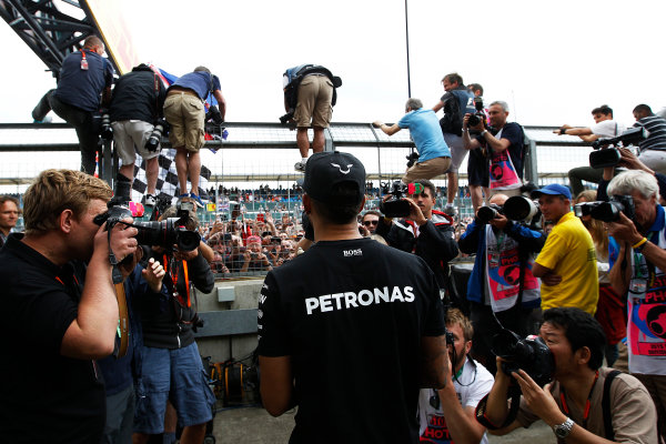Silverstone, Northamptonshire, England. Sunday 05 July 2015. Lewis Hamilton, Mercedes AMG, walks past photographers to get to fans waiting on the track Photo:  Sam Bloxham/LAT Photographic ref: Digital Image _G7C3163
