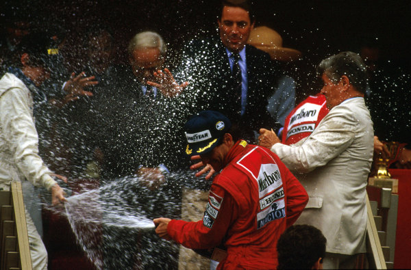 Monte Carlo, Monaco.4-7 May 1989.Stefano Modena (Brabham Judd) 3rd position gives Ayrton Senna (McLaren Honda) 1st position a spraying on the podium. Prince Rainier's bodyguards try to intercept the incoming shower of champagne.Ref-89 MON 18.World Copyright - LAT Photographic