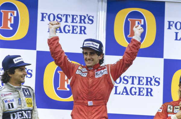 Alain Prost, 1st position, celebrates an unlikely second world championship alongside Nelson Piquet, 2nd position, on the podium.