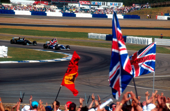 1994 British Grand Prix. Silverstone, England. 8-10 July 1994. Damon Hill (Williams FW16 Renault) carries the Union Jack after a jubilent victory in front of his home crowd. Ref-94 GB 17. World Copyright - LAT Photographic