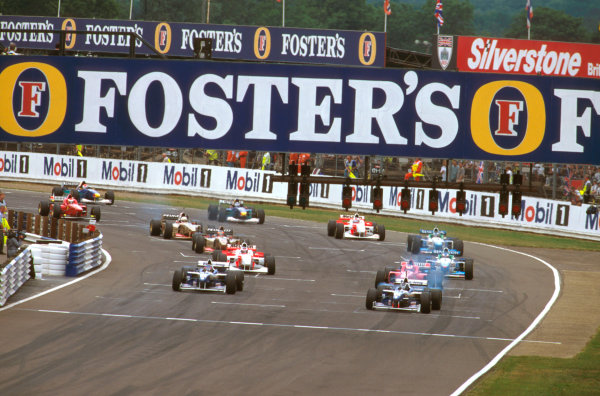 Silverstone, England.12-14 July 1996.Damon Hill and Jacques Villeneuve (Williams FW18 Renault) smoke away fom the front row as Michael Schumacher (Ferrari F310) and Mika Hakkinen (McLaren MP4/11 Mercedes) follow at the start.Ref-96 GB 07.World Copyright - LAT Photographic
