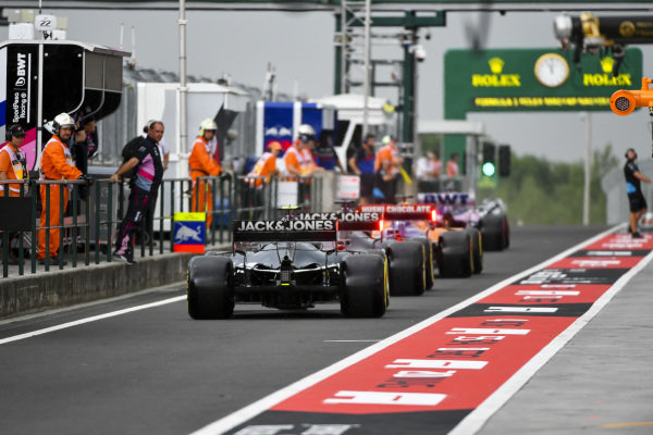 Romain Grosjean, Haas VF-19, and Kevin Magnussen, Haas VF-19, leave the pits