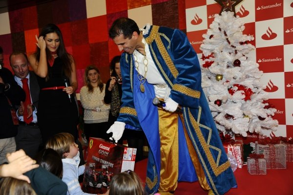 Marc Gene (ESP), Ferrari test driver, hands out presents to children.