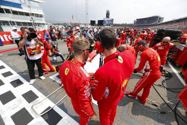 Sebastian Vettel, Ferrari, talks to an engineer on the grid.