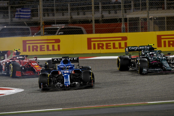 Fernando Alonso, Alpine A521, leads Sebastian Vettel, Aston Martin AMR21, and Carlos Sainz, Ferrari SF21